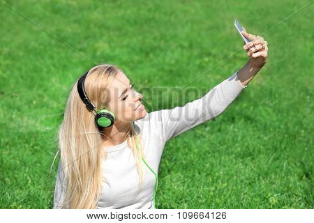Young woman in earphones making selfie on grass