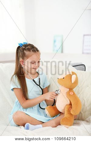 Beautiful little girl with teddy bear sitting on sofa, on home interior background