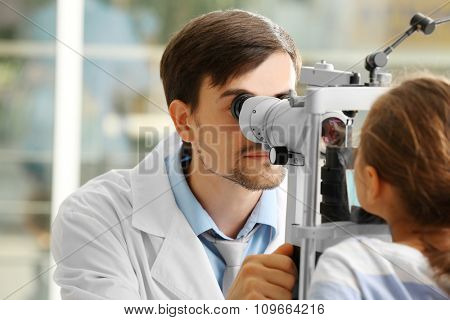 Adult male doctor examing small girl patient
