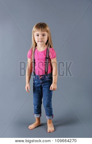 Beautiful little girl on gray background