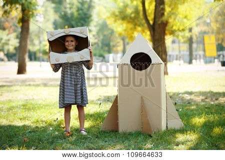 Pretty little girl in box helmet standing near carton rocket in  the park