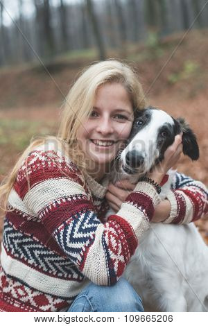 Young woman embrace her cute dog outdoor in the forest
