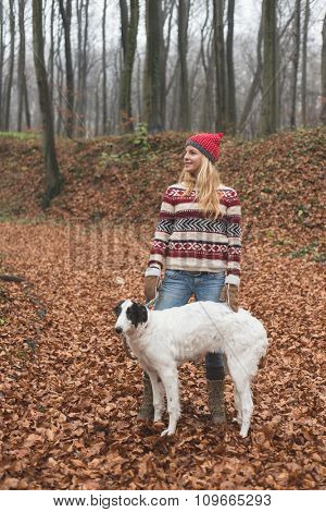 Young woman posing outdoor with her dog in the forest