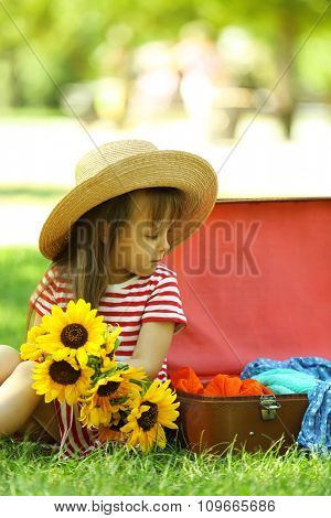 Little girl with sunflowers and suitcase in the park