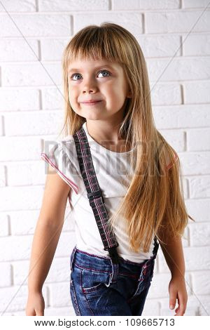Beautiful little girl on light wall background