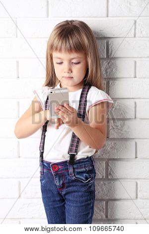 Beautiful little girl with mobile phone on light wall background