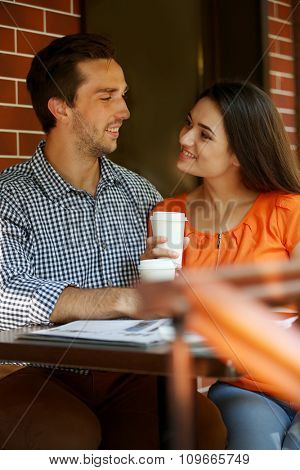 Young couple drink coffee in cafe outdoors