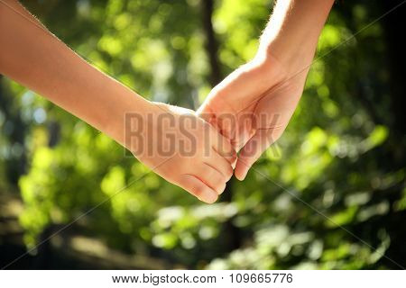 Young couple holding hands on nature background