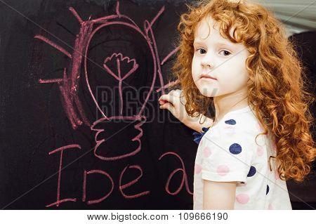 Girl Writes In Chalk On A Blackboard. Education Concept.