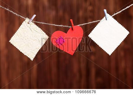 Red heart and blank notes, on wooden background