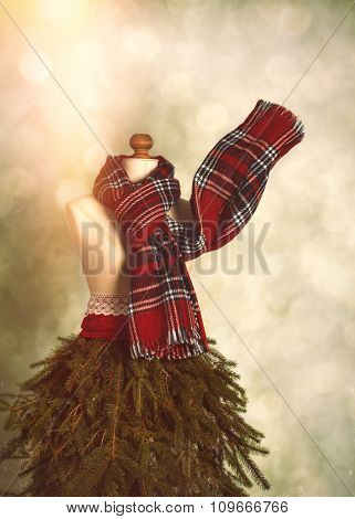 Vintage mannequin dressed for a festive winter with tartan scarf