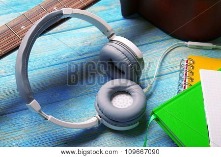 Headphones, guitar and notebook on blue wooden background, close-up