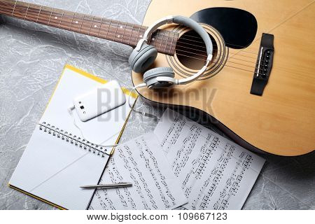 Classical guitar and headphones with phone on grey background