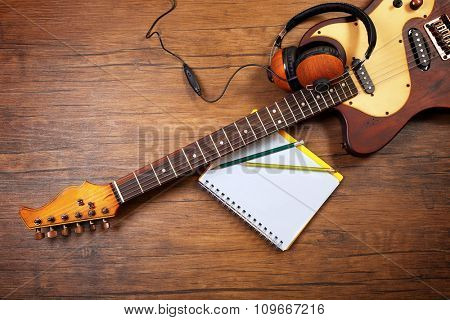 Electric guitar and headphones on wooden background