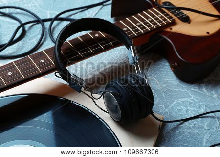 Electric guitar and headphones with music accessories on grey background