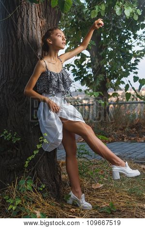 Fashion portrait shoot of a beautiful girl posing near tree during city fashion photoshoot with greenery at background