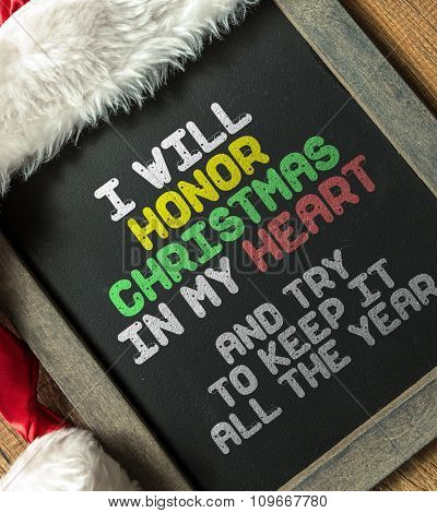 I Will Honor Christmas In My Heart And Try to Keep It All the Year written on blackboard with santa hat