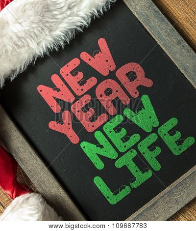 New Year New Life written on blackboard with santa hat