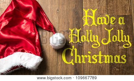 Have a Holly Jolly Christmas written on wooden with Santa Hat