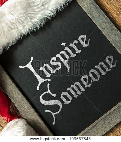 Inspire Someone written on blackboard with santa hat
