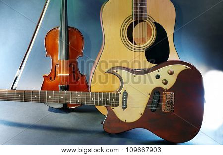 Electric and acoustic guitars, violin on blue background