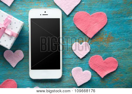 Smart phone with blank screen and hearts on old wooden table