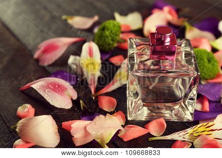 Bottle of perfume and flowers petals on wooden background