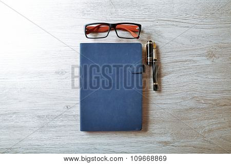 Workplace - blue notebook, pen and eyeglasses on grey wooden background