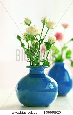 Beautiful roses in turquoise vases on window background