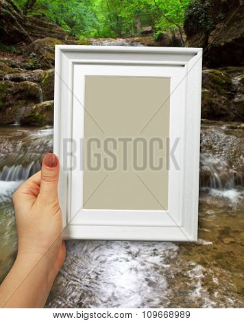 Wooden frame in beautiful woman hands. Waterfall on the background