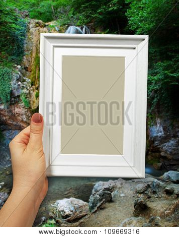 Wooden frame in beautiful woman hands on the background natural spring waterfall