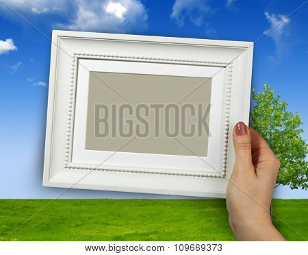 Wooden frame in beautiful woman hands on the Sky and tree background
