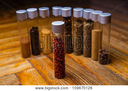 Assorted spices in bottles on wooden background