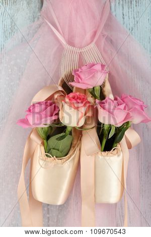 Decorated ballet shoes with roses in it hanging on blue wooden background