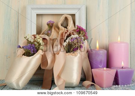 Decorated with flowers and candles ballet shoes in frame on creamy wooden background