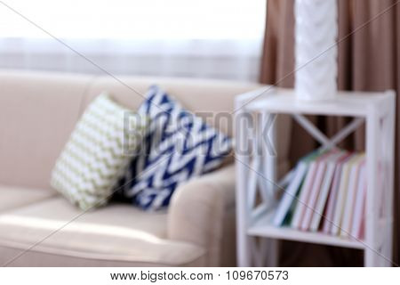 Comfortable sofa  with different pillows in the room, unfocused