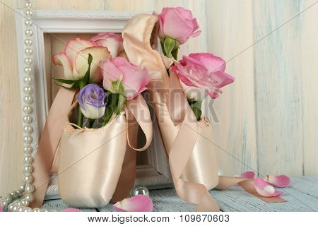 Decorated with flowers ballet shoes in frame on wooden background