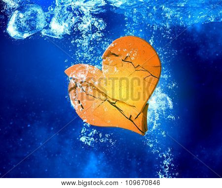 Broken heart sinking and dissolving in clear blue water