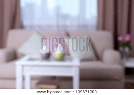 Unfocused beige sofa with beautiful pillows and decorative vases on the table in front of it in the room