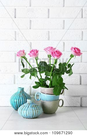 Beautiful roses and vases on brick wall background