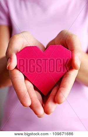 Closeup of plastic puzzle heart in female hands