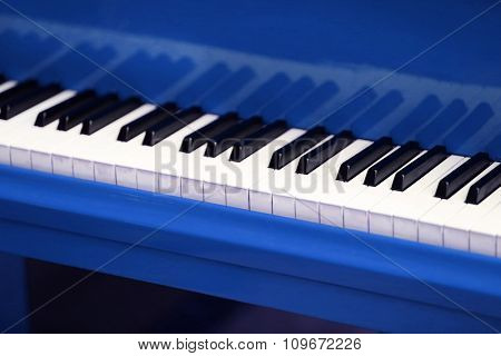 Piano keys of blue piano close up