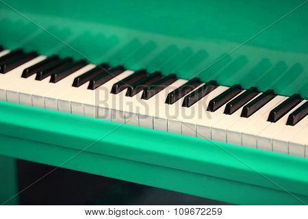 Piano keys of green piano close up
