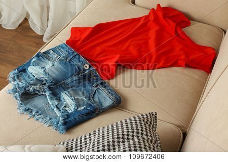 Jeans shorts with red T-shirt on sofa in room