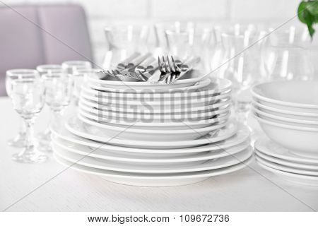 Clean plates, glasses and cutlery on white table