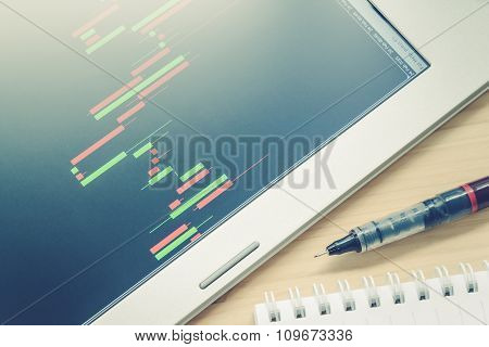 Stock Or Forex Graph Or Candlestick Chart In Tablet Screen And Pen And Notebook On Blue Vintage Styl