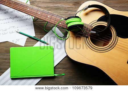 Classical guitar and headphones with music notes on wooden background