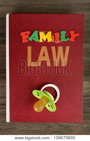 Book of law, a dummy and colourful letters regarding child-custody and family-law concept