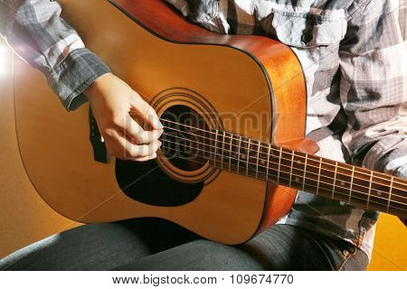 Guitarist plays guitar in the room, close up