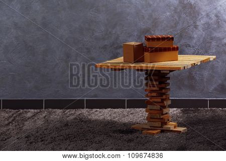 Small wooden table and boxes on grey wall background